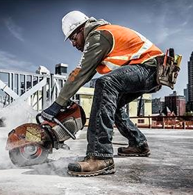 Man cutting concrete with concrete saw